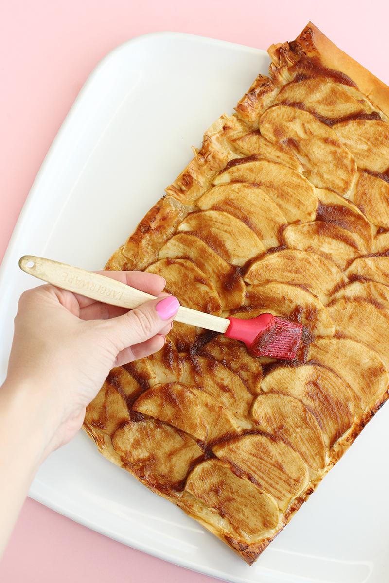 Brushing jam on French apple tart.