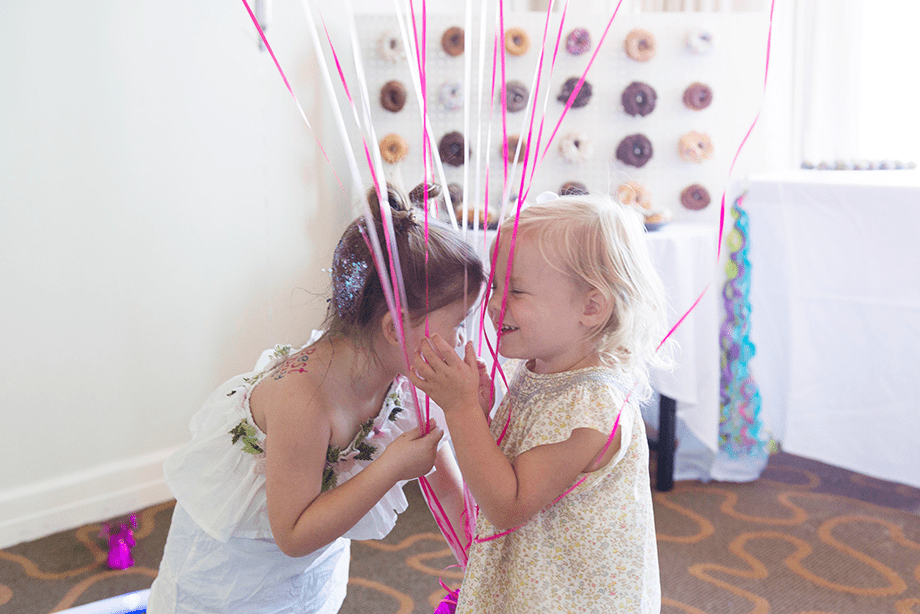 Best friends in front of a donut wall.