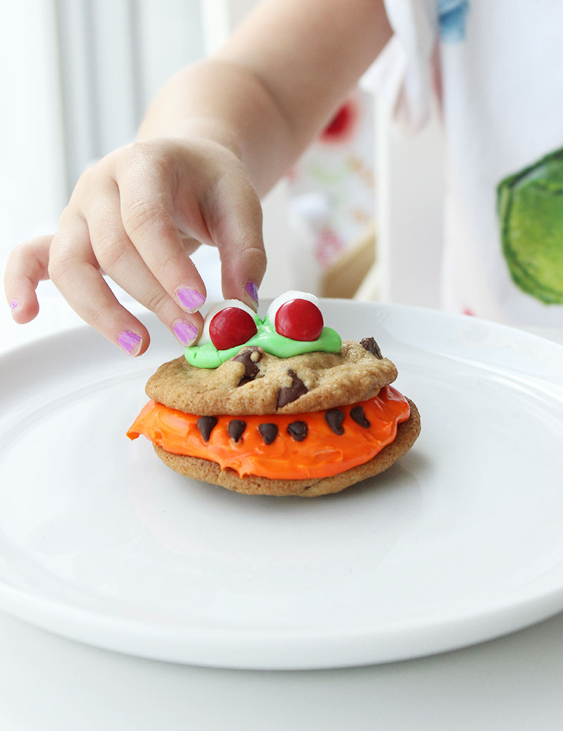 A young toddler making scary monster cookies.