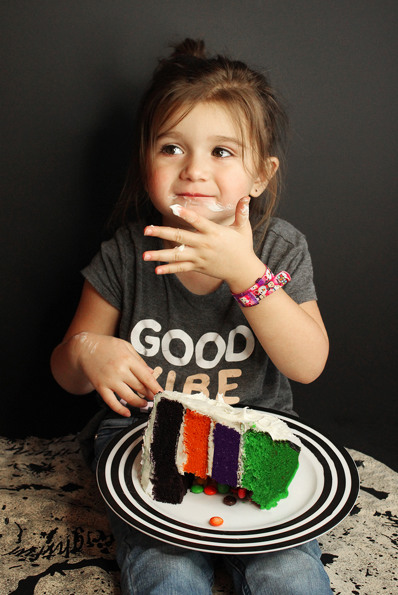 A toddler eats Halloween layer cake.