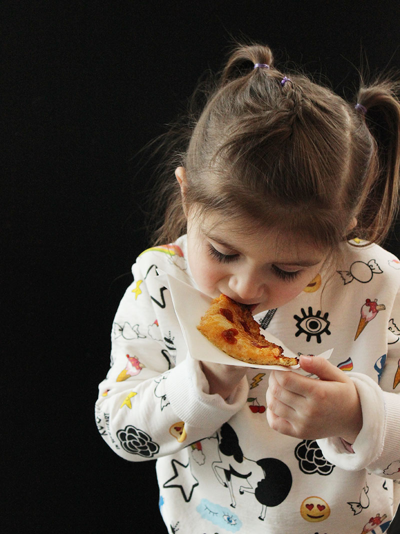 A toddler eating cauliflower crust pizza with pepperoni hearts.