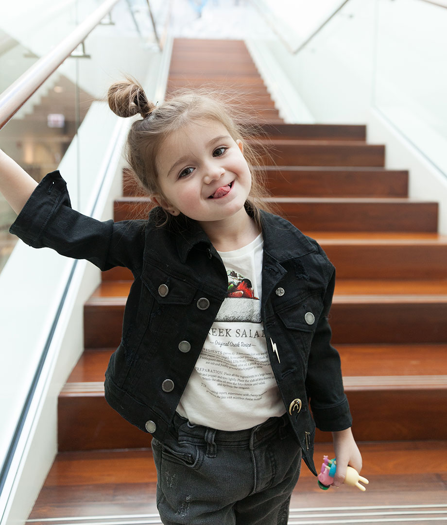 A toddler wears a denim jacket and a t-shirt in Chicago's Greektown.