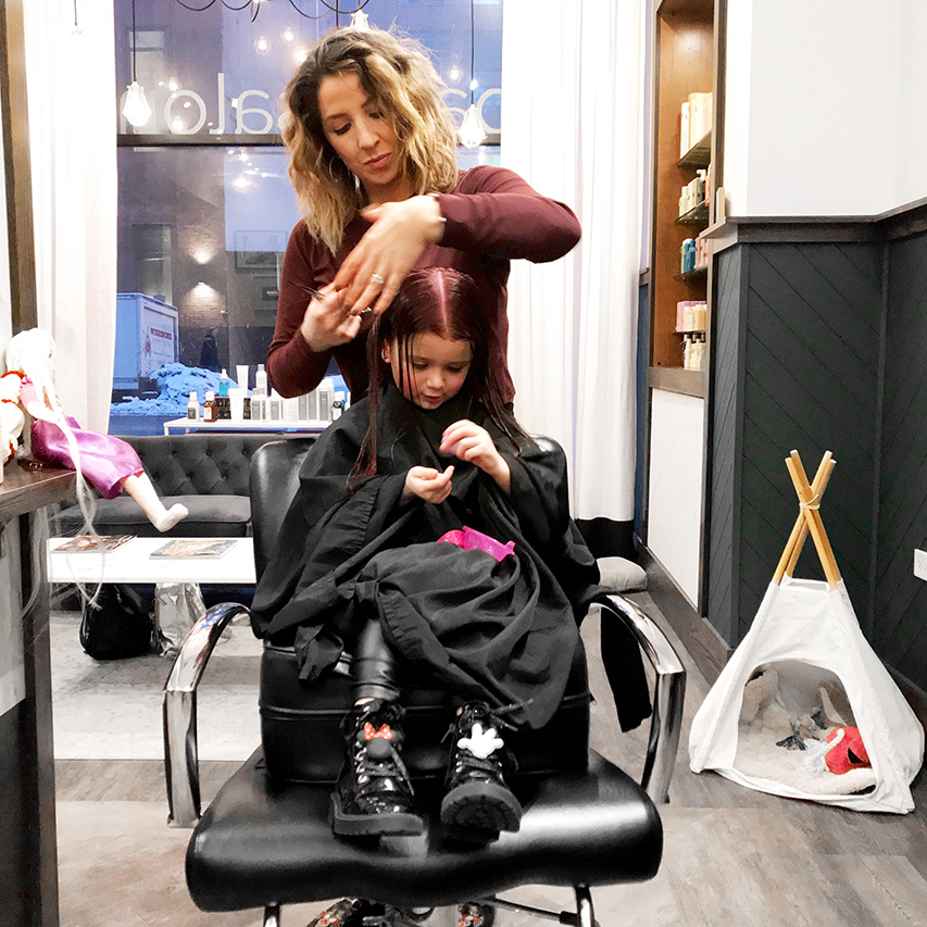 Zelda of Glitter and Bubbles sits in a chair at Base Salon while a hairstylist dyes her hair pink with vegan hair color.