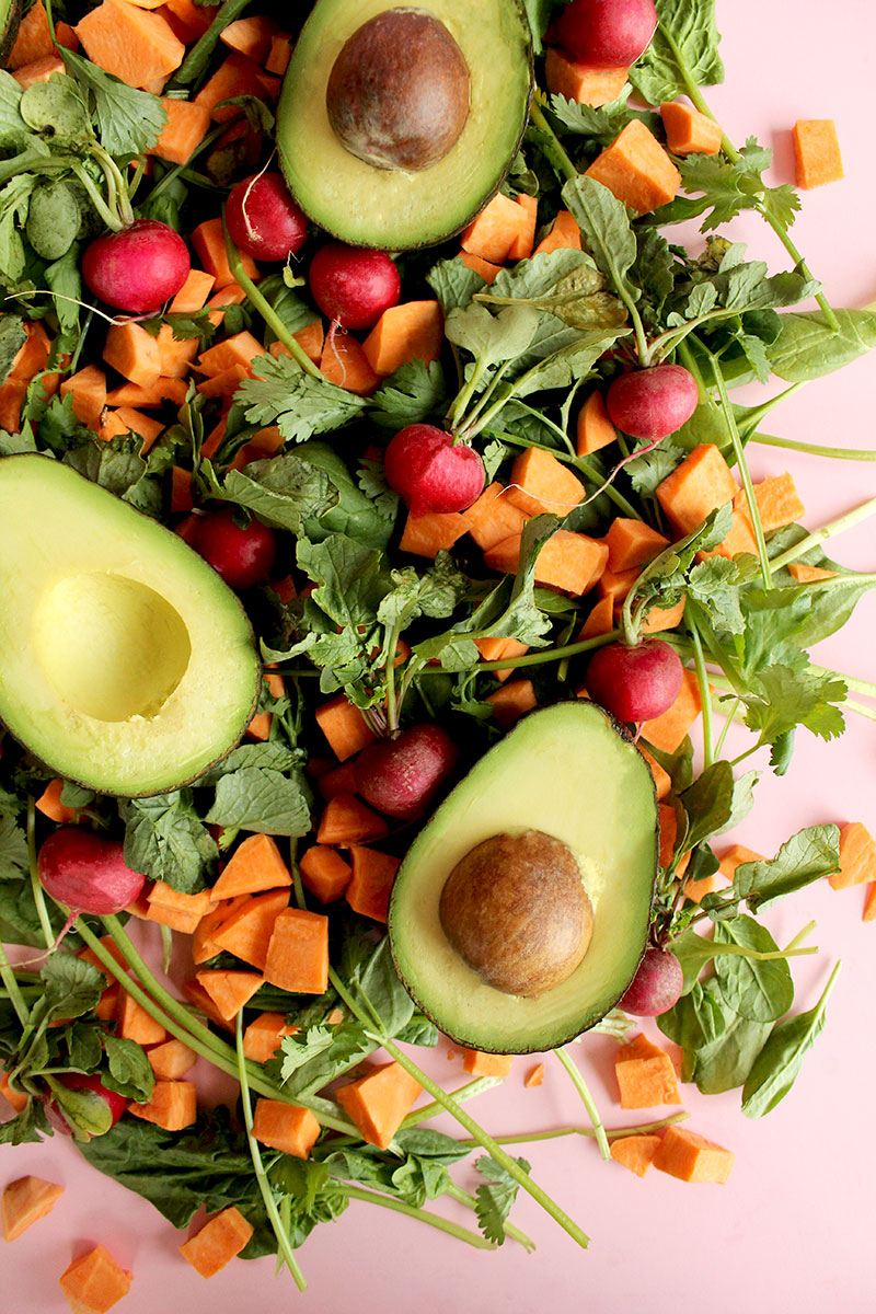Spinach, beets, sweet potatoes and avocados sit on a pink background.