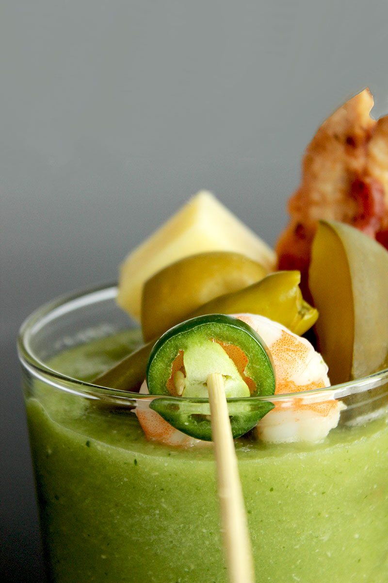 The best garnishes for a Green Bloody Mary, including shrimp, jalapeno, bacon, white cheddar and olives.