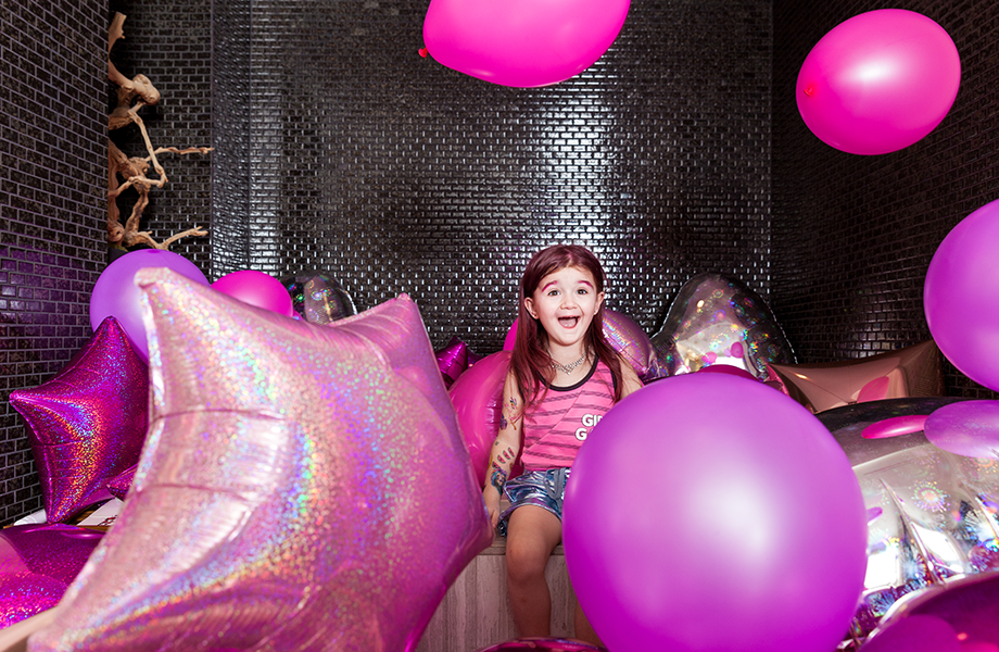 Zelda of Glitter and Bubbles sits on the edge of a bathtub filled with balloons.