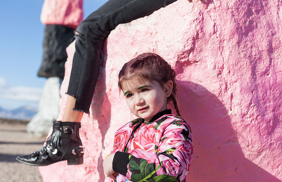 A pink haired toddler stands in front of a pink rock in Las Vegas.