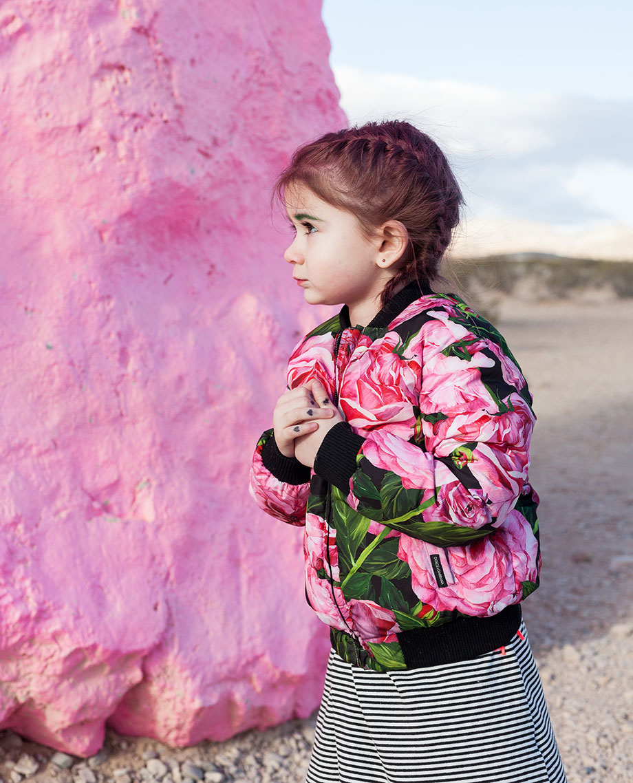 Zelda of Glitter and Bubbles stands by a pink rock in a floral bomber jacket.