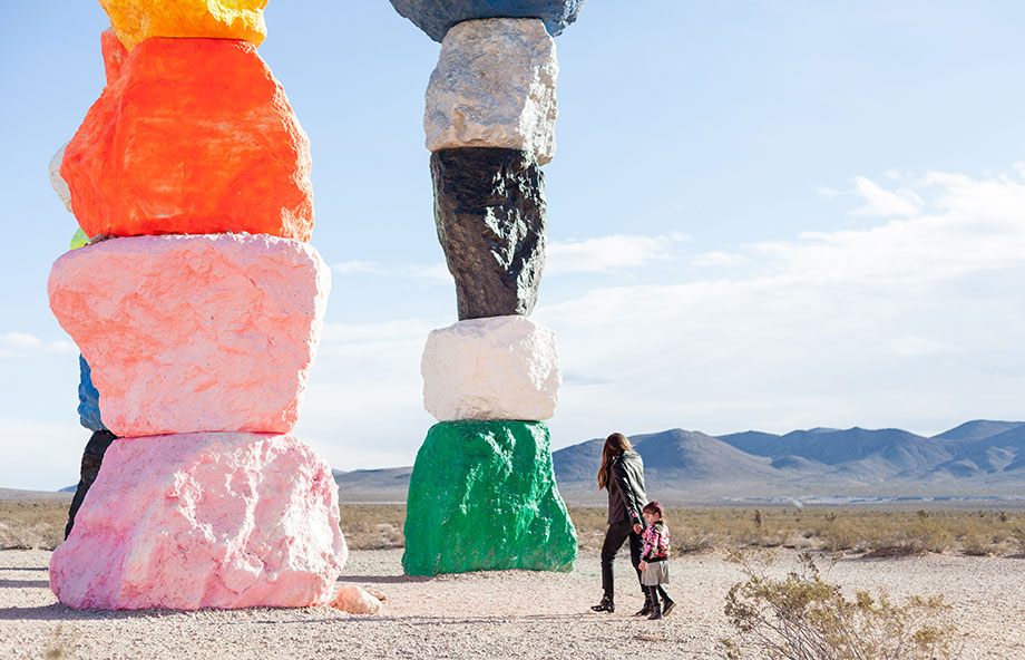A Kid Friendly Las Vegas Travel Guide featuring Corri McFadden and Zelda standing in front of Seven Magic Mountains.