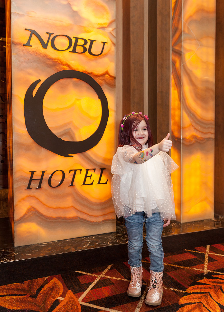 A pink haired toddler stands by the Nobu Hotel sign in Las Vegas.