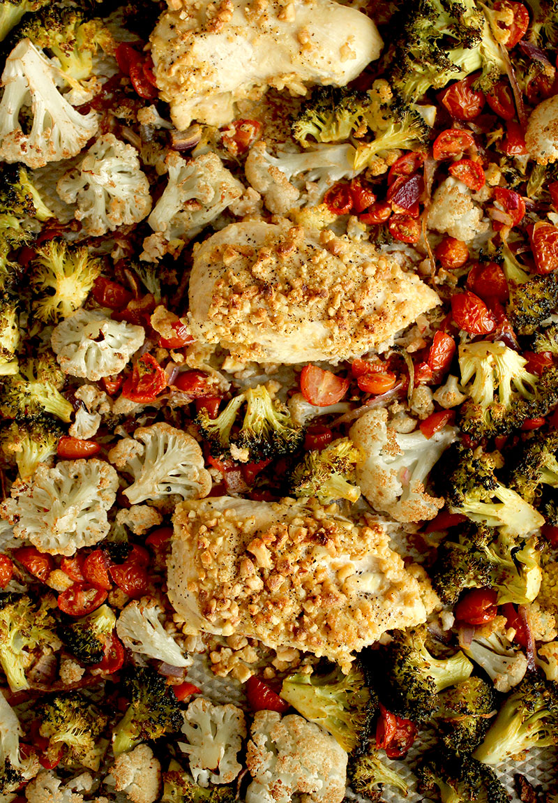A sheet pan is filled with cashew chicken and roasted vegetables for an easy dinner recipe on Glitter and Bubbles.