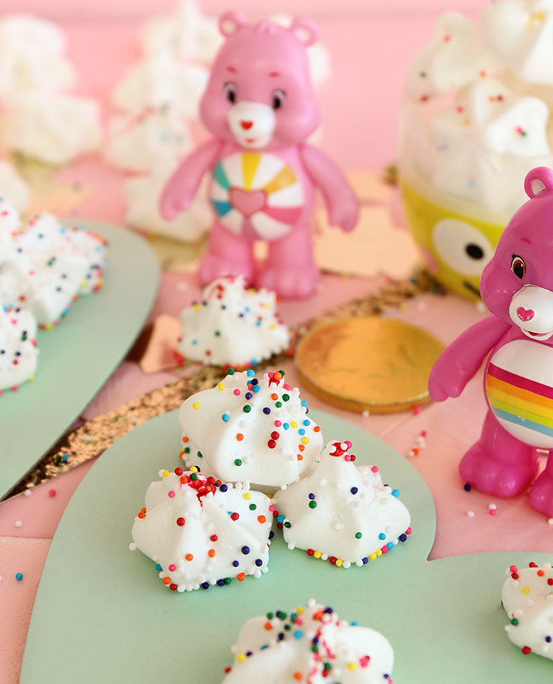 Two Care Bears stand by rainbow meringues for St. Patrick's Day.