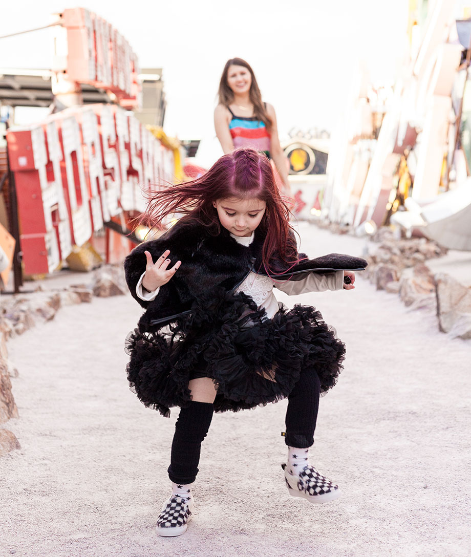 A little girl plays at the Neon Museum in Las Vegas wearing a tutu and Vans.