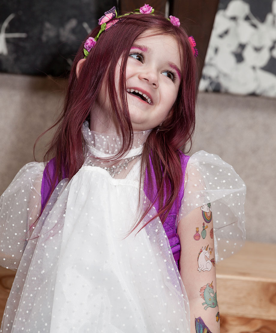A toddler with pink hair wears a flower crown and a white tulle top.