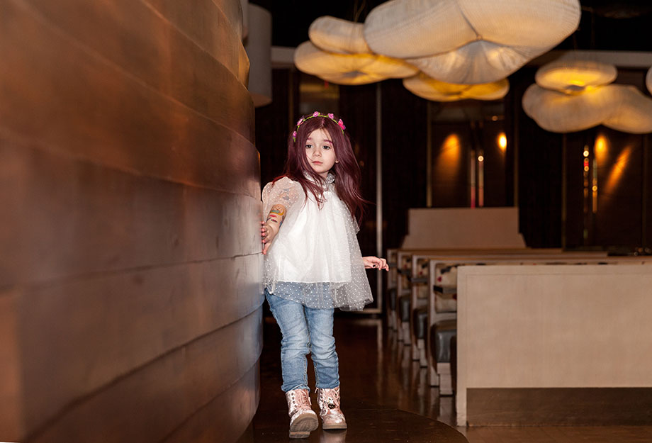 A toddler stands in a Nobu Hotel restaurant.