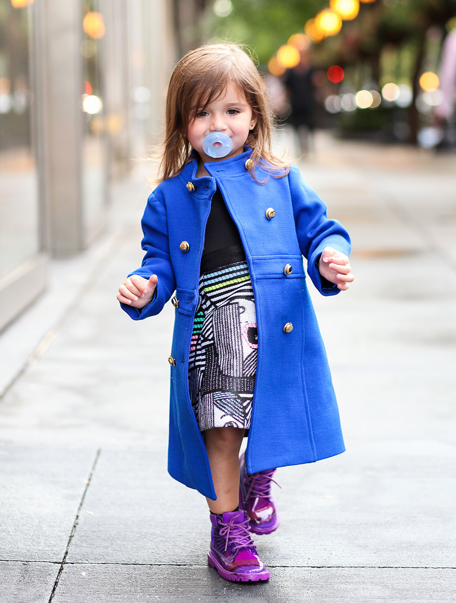 Zelda of Glitter and Bubbles stands on the sidewalk wearing a blue coat with a pacifier.