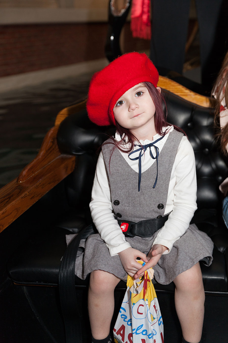Zelda of Glitter and Bubbles sits in a gondola wearing a red hat and a checked dress.