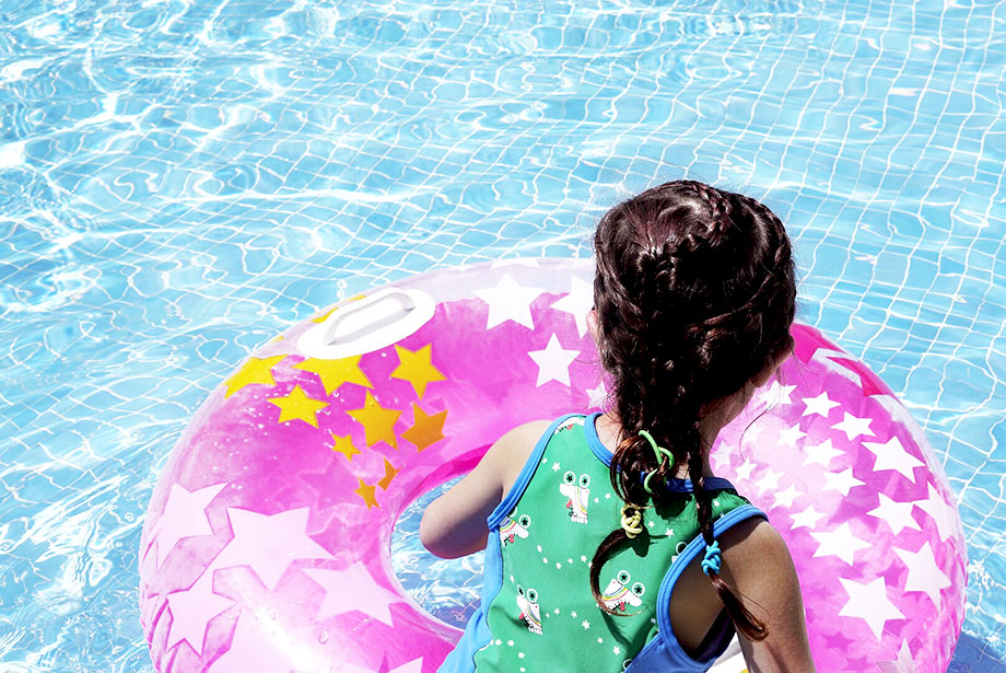 A little girl with braids in her hair sits in a pool float.
