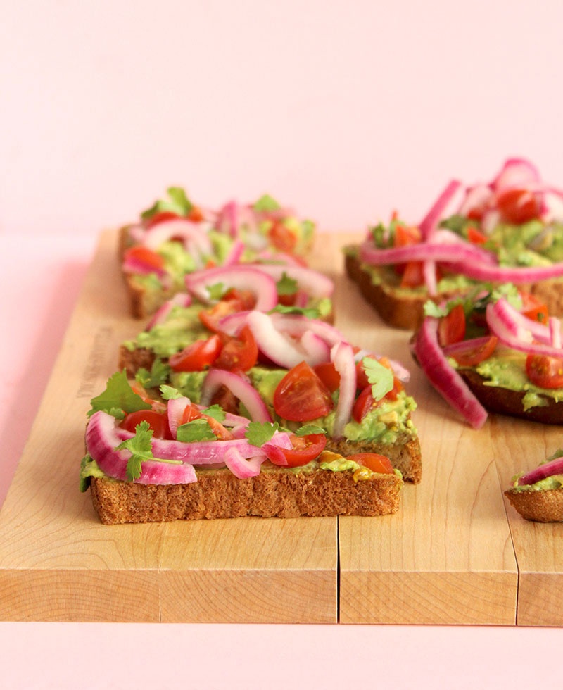 Sliced avocado toast sits on a cutting board from Williams-Sonoma with pickled onions.