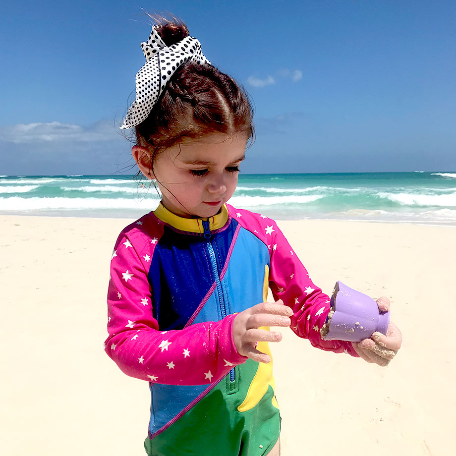 A toddler stands on the beach in Punta Cana wearing a top knot.