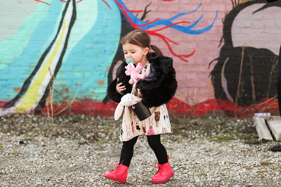 A toddler stands in front of a graffiti wall wearing bright boots.