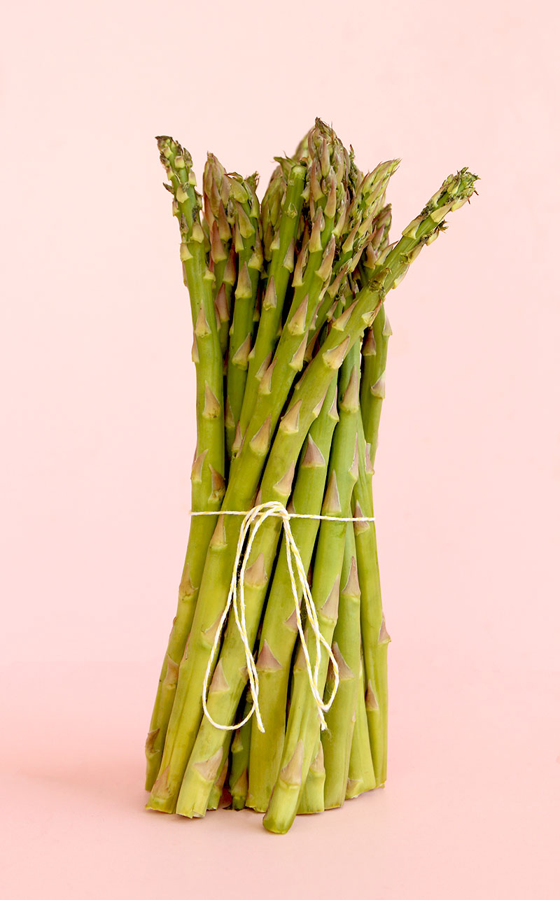 A stack of asparagus stands against a pink backdrop.