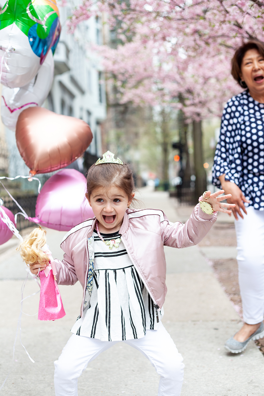 Zelda of Glitter and Bubbles wears a pink jacket and striped shirt while holding balloons.