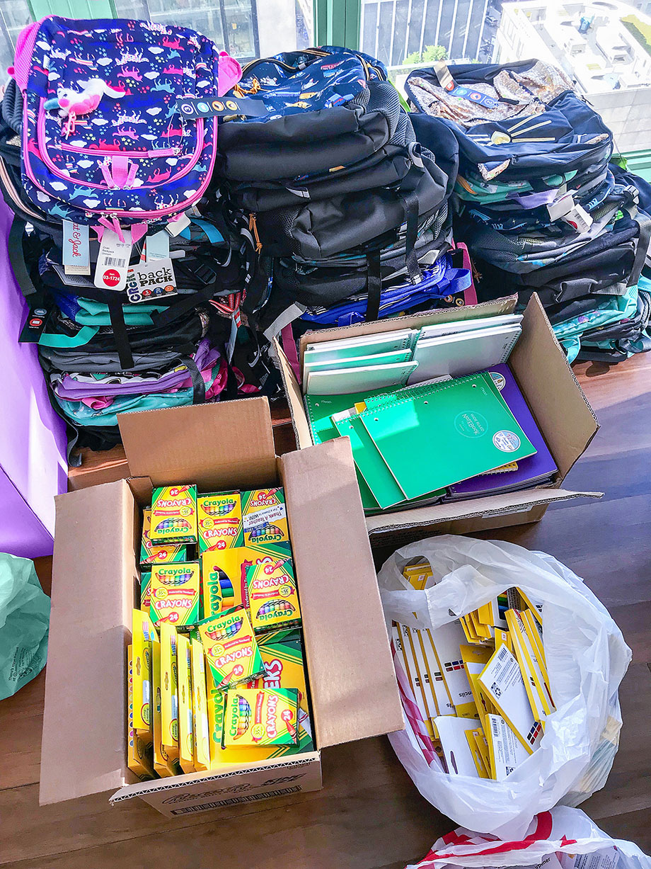 A box of backpacks sits on the floor for the Youth of Englewood.