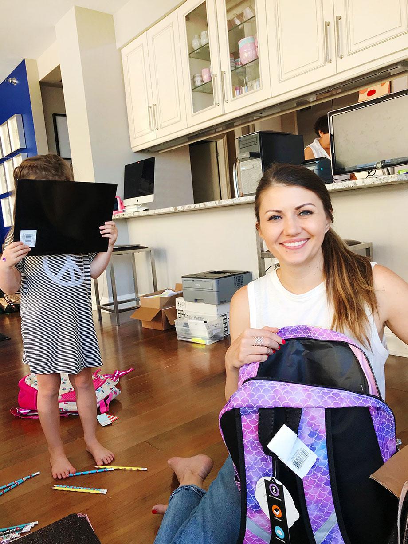 Corri McFadden packs back to school backpacks for The Youth of Englewood.