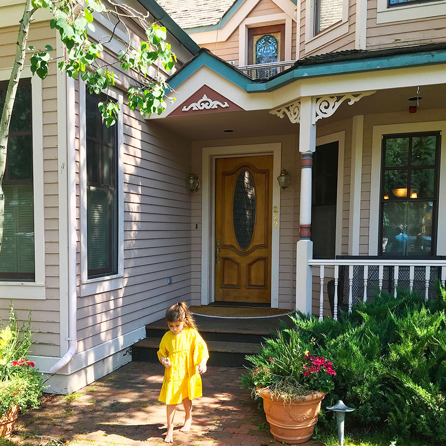 Zelda of Glitter and Bubbles stands in front of a house in Aspen, Colorado.