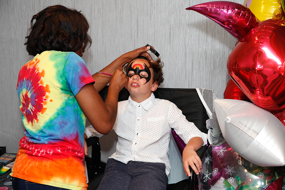 A little boy gets his face painted at Zelda's birthday party on Glitter and Bubbles.