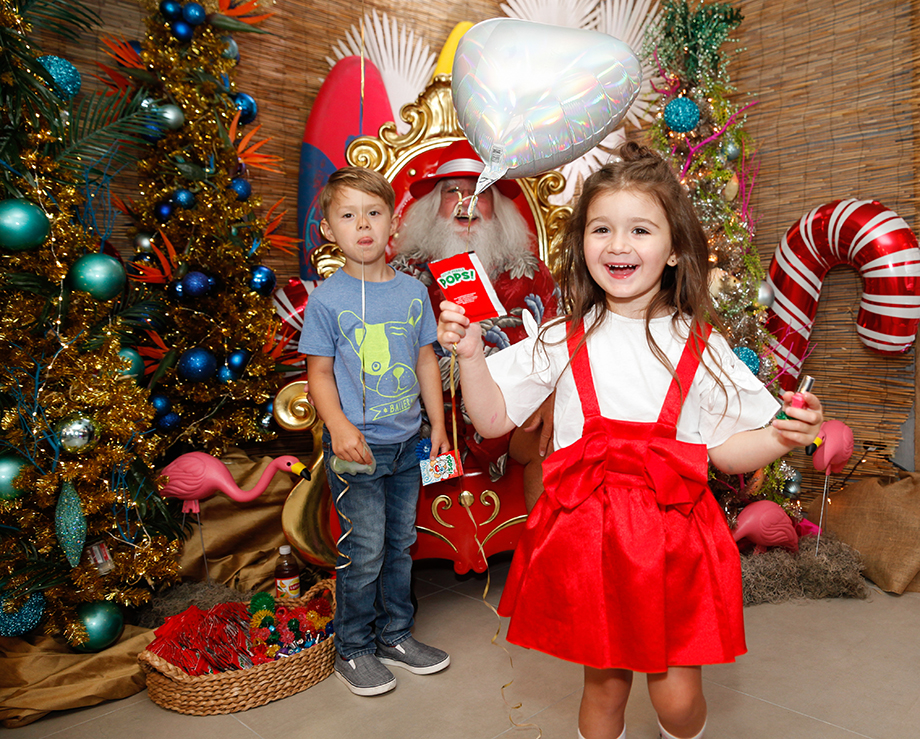 Zelda of Glitter and Bubbles wears a red dress at her Christmas in July themed birthday party at the Swissotel.