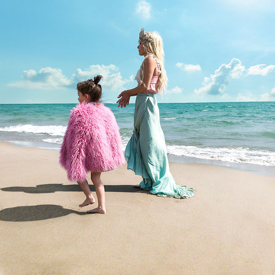 Zelda of Glitter and Bubbles walks on the beach with a mermaid.