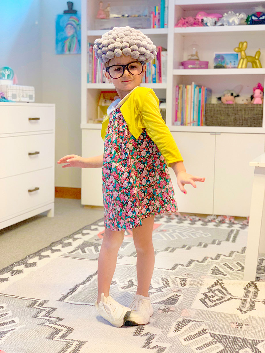 A little girl in a floral dress dresses up as a grandma on Glitter and Bubbles.