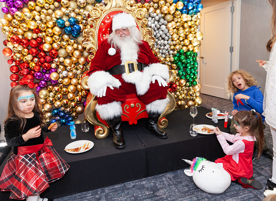 Santa sits in his chair surrounded by children.