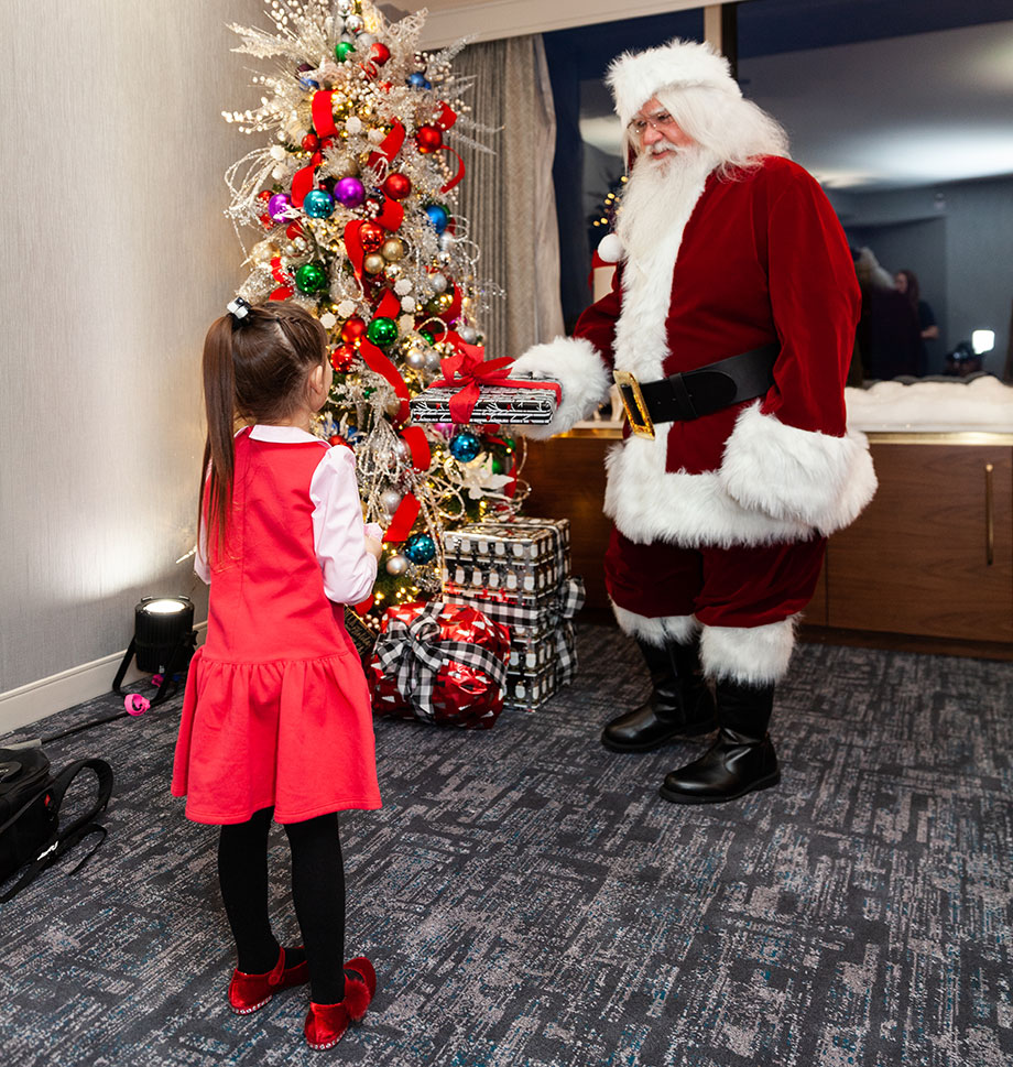 A little girl gets a special visit from Santa at the Swissotel Santa Suite.