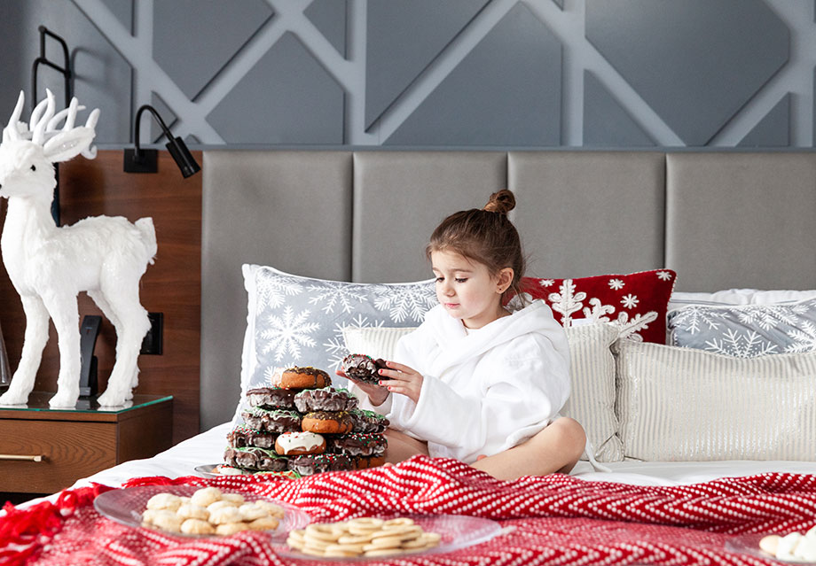 Zelda counts donuts while laying in bed at the Swissotel Santa suite.