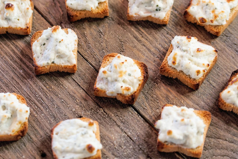 Cheese topped tiny toasts.