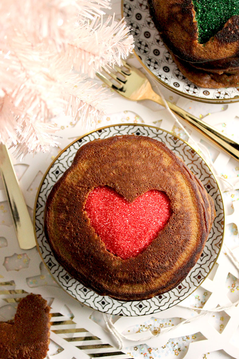 A sprinkle filled heart is shown on top of a stack of gingerbread pancakes for Christmas morning.