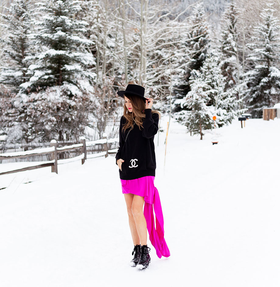 Corri McFadden stands outside in Aspen in a pink skirt and a black Chanel sweater in Aspen, Colorado.