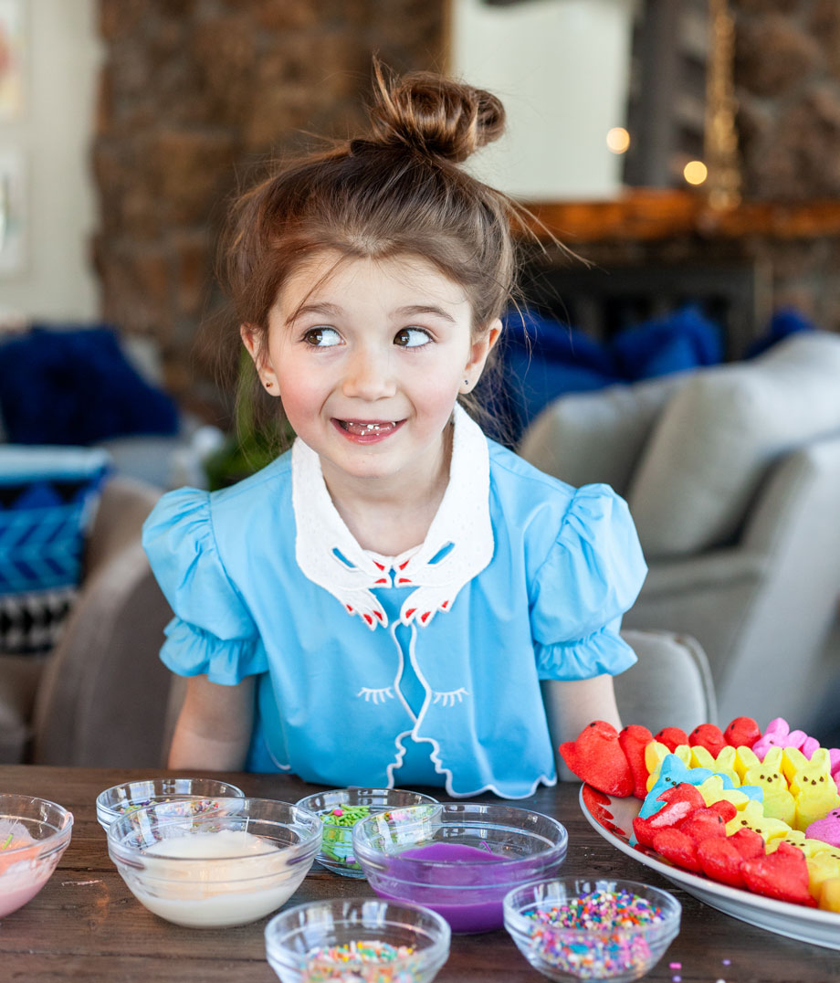 A little girl wears a blue Easter dress while making frosted peeps on Glitter and Bubbles.