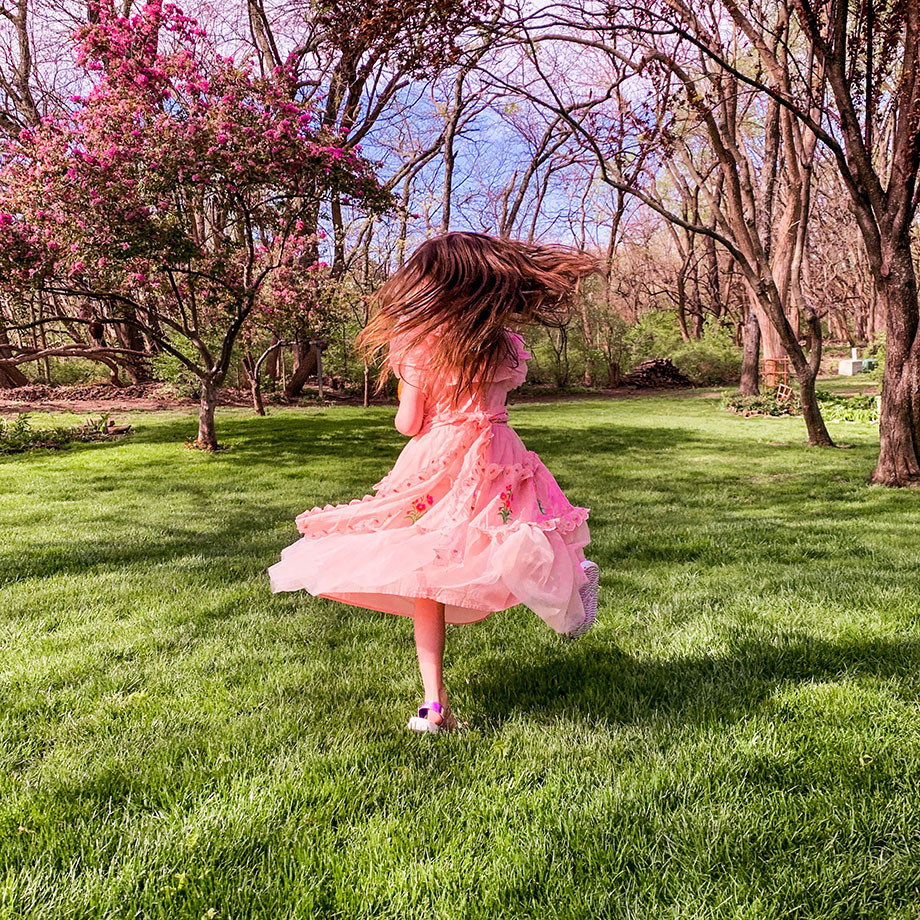 A little girl plays outside in a pink dress on Glitter and Bubbles.