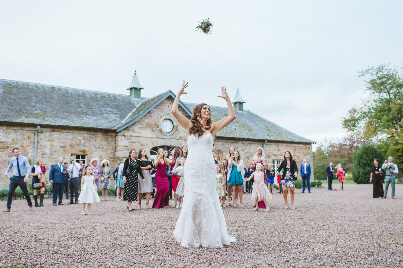 Bouquet toss at a wedding at Colstoun House
