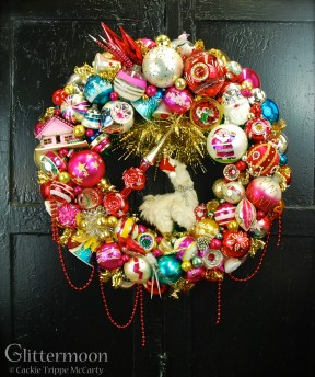 "The Lama Wreath, made especially to hang in the Beekamn 1802 Mercantile, Sharon Springs, NY. The largest wreath I have made to date and just loaded with all kinds of fab goodies; with a miniature Polka Spot (the llama) dress in her holiday finery of rhinestones and a Santa hat. About 27"" diamater $525 *SOLD*"