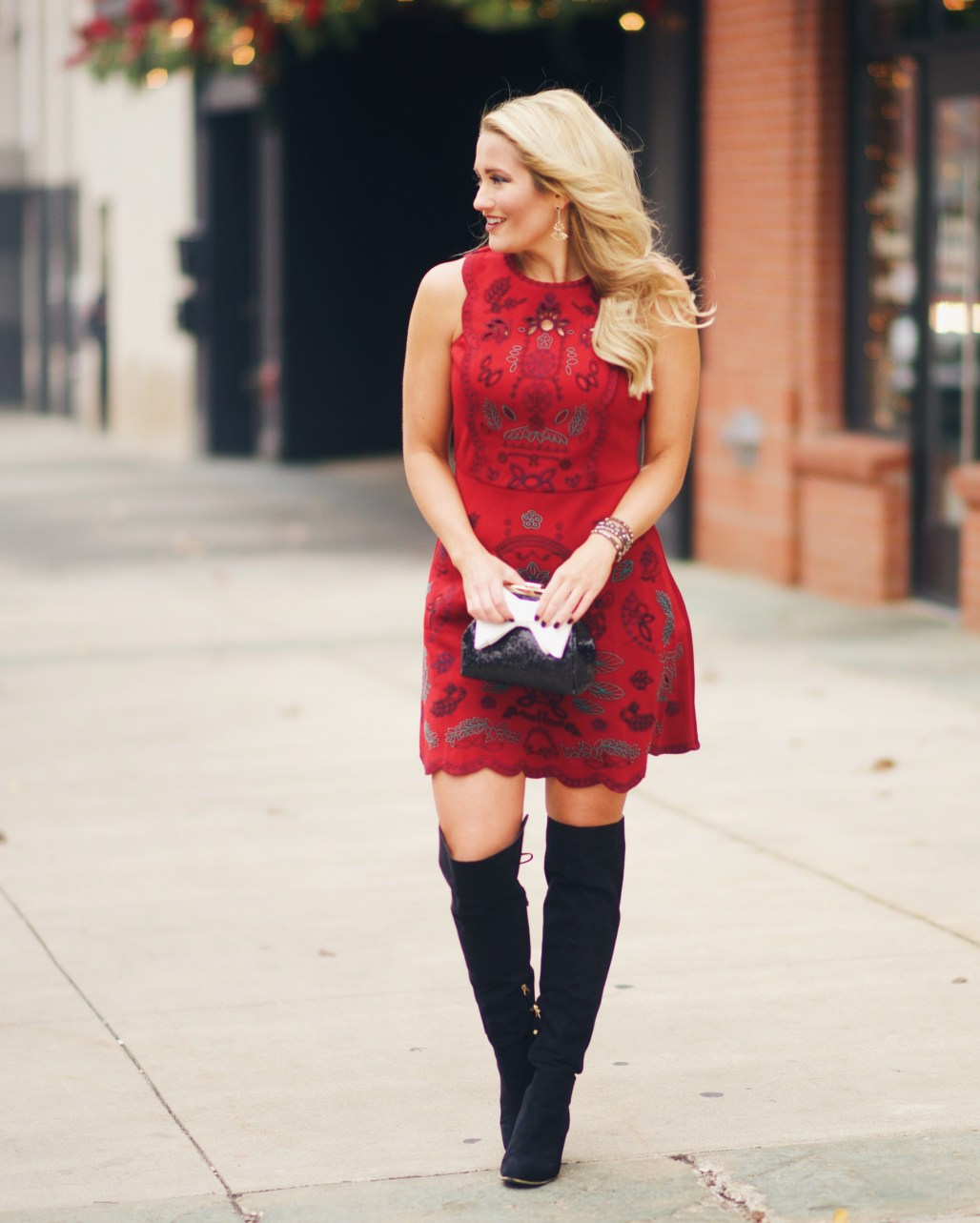Red embroidered dress with over the knee boots and sequin handbag