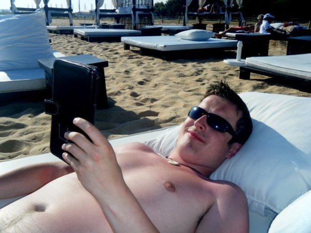 Lee reading the Kindle on the beach in the Algarve, Portugal.