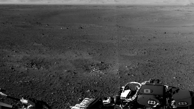 "These are the first two full-resolution images of the Martian surface from the Navigation cameras on NASA's Curiosity rover, which are located on the rover's ""head"" or mast. The rim of Gale Crater can be seen in the distance beyond the pebbly ground. (NASA/JPL-Caltech)"