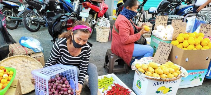 Women sell fruit and vegetables on a sidewalk in the Philippines, where workers in the informal economy are in danger of having their livelihoods destroyed by the impacts of COVID-19.