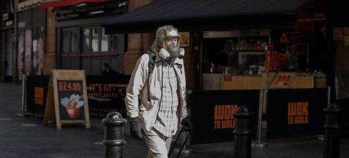 A masked man walking in London's West End