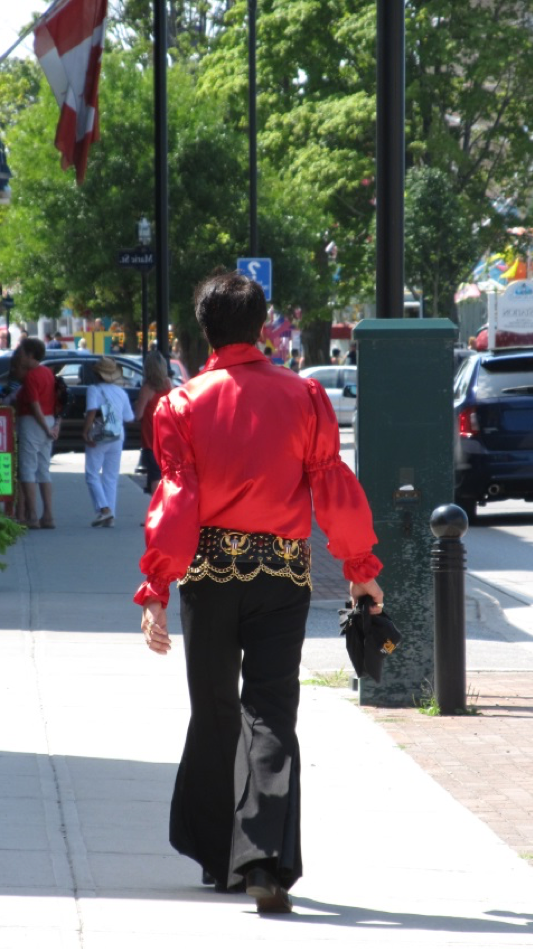 An elvis impersonator walking away from the camera